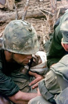 Cover image, LIFE magazine. American Marines aid a wounded comrade during Operation Prairie near the DMZ during the Vietnam War, October 1966.