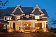 I love craftsman style houses. The dormers and columns frame the entrance to the house. Wonderful lighting too.
