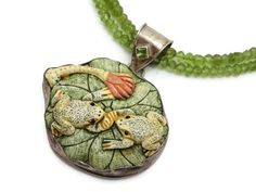 A beautiful vintage necklace, featuring a double strand of peridot beads, sterling silver hardware, and a carved and dyed bone or resin pendant