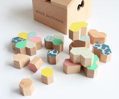 積み木と木箱がセットになったmina perhonen TSUMIKI。六角形をベースにした、ドロップ型、ハート型のピースがお子様の想像力を育みます。