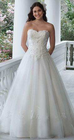 Resemble Cinderella in this tulle ball gown with a sweetheart neckline, beaded lace appliques, full tulle skirt, and chapel length train.