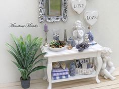 Dollhouse miniature elegant wooden sideboard 1:12. Lavender arrangement. Many details and accessories according the photo, including the vintage table wall mirror and wall decorations. Two angel statues, plant Sansevieria (Tenura) in the pot. Size h 6.5cm, w 10cm, d 4.5cm (2.6 x 4 x 1.8). This item is not suitable for children under 14 years. The small parts inhalation or swallow risk.