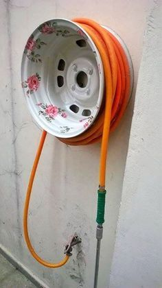 15 Ways To Repurpose Household Items For Your Garden | Postris - Garden Hose Holder From Old Rim
