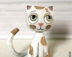 Mini gato sentado manchado blanco y beige