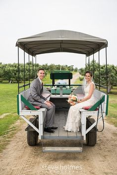 Bride and groom ride together to reception in a wagon pulled through an orchard. Photo by Steve Holmes Photography