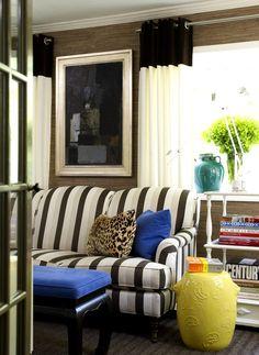 Полосатый диван в гостиной комнате дополнен яркими аксессуарами