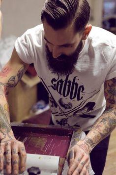 Tattoos and beard.