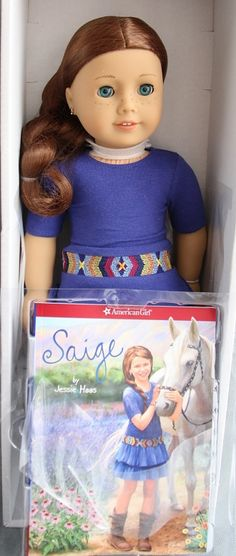 American Girl of the Year Doll 2013 Saige w/ her book. The illustration has a side part. Love that side braid & freckles :)  She's very fair, just like a real redhead! GOTY 2013