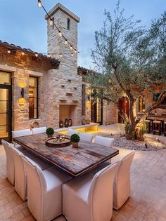 Mediterranean Patio with Transom window, Reclaimed Farm Table, French doors, exterior stone floors, Arched window