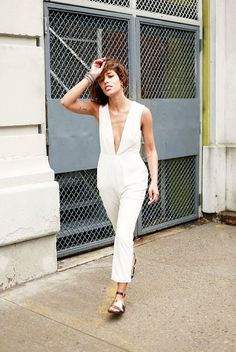 Evening jumpsuit with plunging neckline paired with black and gold sandals