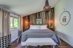 Beautiful gingham drapery, a masculine chandelier, and a paneled accent wall dress up this simple yet chic master bedroom.