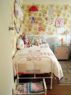 Adorable little girls room: love the patterned wall paper, stuffed babushka on the bed, wall hangings.