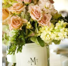 10. Cozy: The monogram gracing these low centerpieces gives the whole table a homey feeling. These low centerpieces are  filled with peach, cream, and green flowers, including hydrangeas, roses, orchids, and hypericum berries.