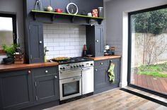 Dark gray cabinets, butcher bl9ck countertop and white subway tile. Renovation success featuring our Rangemaster Professional Deluxe in Stainless Steel complemented by handpainted kitchen cabinets and Black American Walnut worktops.