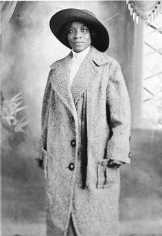 African American woman standing in hat and full length coat. c.1900