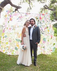 The bride's sister deconstructed more than 1,000 silk flowers and then glued the petals together curtain-style to create this photo booth backdrop.