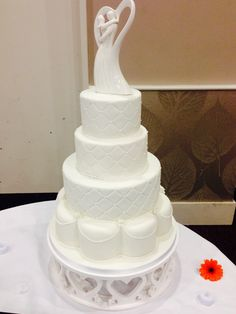A Simple white wedding cake with a quilt effect design.