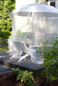 mosquito net over umbrella around eating table