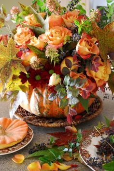 Pumpkin Vase Centerpiece - Floral Arrangement of Fall Colors and leaves and apples and peach roses.