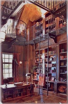 Two story library with latter up to balcony. Great way to use the vaulted area of a room.