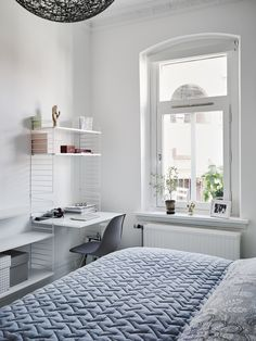 bright bedroom office space string shelves blue bedspread white walls large windows