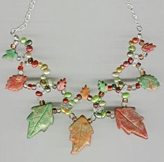 """An experiment with ring-sized memory wire and multi-strand bridges.  The leaves (large and small) are, of course polymer clay with a makume game outer layer (used pearl-ex, metallic leaf) Other than the clay and memory wire.. Plus dyed freshwater pearls (top-drilled) in cranberry, goldenrod and several greens, a silver-toned 2-strand bridge with glass """"e"""" beads. Happy to share tips and techniques! And NotJustPartz has the pearls, leaves, beads and instructions if you're up to it."""