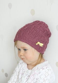 This is knitting pattern for simple slouchy baby hat with velvet ribbon bow. Easy to knit with basic k and p stitches, worked in flat.