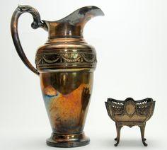 Lote composto por jarra em metal prateado espessurado a prata e pequeno centro. 40 cm de altura.