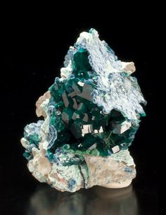 Emerald green Dioptase crystals completely fill a small vug along with velvet spheres of Shattuckite, radial sprays of Malachite, and Plancheite.