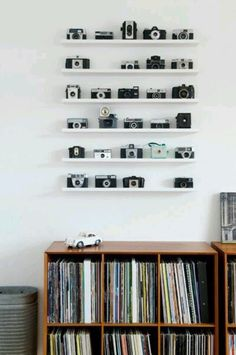 Lining up collectibles along a set of shallow shelves lets them serve as wall art. In the display of cameras above, spotted on Alt de Damerne, the addition of a single turquoise camera and the omission of cameras from two spots makes the arrangement even more artful. The LACK shelf from IKEA would work well for this type of presentation.