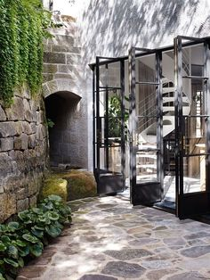 Outdoor design: architecture, old stonework, folding french doors and greens! Steel Windows, Windows And Doors, Interior Exterior, Exterior Design, Exterior Doors, Outdoor Spaces, Outdoor Living, Indoor Outdoor, Casa Patio
