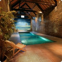 Creative Indoor Pools Design in Luxurious Hotel:Sea Theme Indoor Pool Design With Traditional Brick Wall Lounge Chairs Cream Cushions And Stairs