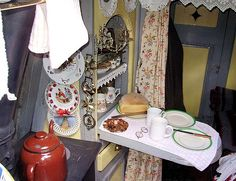 This is the interior of a traditional working narrowboat.  The fold-down cupboard door becomes a work surface or a dining table for two.  This idea would work well in any tiny kitchen.