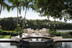 Lakefront backyard boasts an in ground pool fitted with a black octagon hot tub fixed in front of a raised platform finished with white chairs topped with cream curtains and surrounding white accent tables.