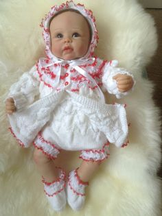 This little matinee set comprises of a matinee coat, frilly knickers, bonnet and slip on shoes in white and trimmed with red and white Will fit 0-3 month baby girl or a 22 inch reborn baby doll  A delightful little set for any special occasion. Please visit my shop to view other baby outfits.  https://www.etsy.com/uk/shop/Meganknits4charity?ref=si_shop  Thank you for your interest and please call again soon.  Purchase any two outfits at the same time to qualify f...