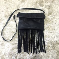 Fringe Crossbody Bag - Black Black fringe crossbody bag. Has two different compartments as shown in the pictures. Both compartments have a button snap. And then once those are closed you can fold over the top which has a magnetic clasp. After folding over it would look as shown in picture one. The strap is removable so it can be carried as a clutch as well. The inside is black with tiny white arrows as the pattern. Feel free to ask any questions!  Bags