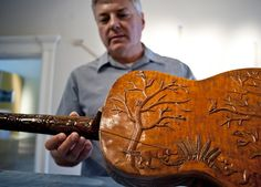 "Thomas Queen, curator for the ""Appalachian Strings"" exhibit at the Decorative Arts Center in Lancaster, Ohio, examines a hand-carved guitar dating from 1894. The guitar, constructed in Van Wert, Ohio by W.S. McCleary, will be on display with other traditional Appalachian instruments."