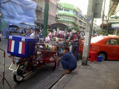 Street vendor prepares sweetened iced-drink, while a customer waits at the roadside. The cart, his livelihood.