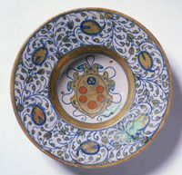 Plate with the Coat of Arms of Pope Clement VII Medici Made in Deruta, Italy, Europe 1523-24 Tin-glazed and lustered earthenware (maiolica)1 7/8 x 8 7/8 inches. Pieces that display this decoration survive in various shapes and sizes, all belonging to what may have been a large papal service. Related designs without a coat of arms were also produced at Deruta.