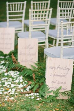 Along the aisle, short love quotes are calligraphed onto plywood, and decorated with driftwood and ferns {Facebook and Instagram: theweddingscoop}
