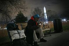 A homeless man sits on a bench with a cup of chili that he received from the Salvation Army in Washington...
