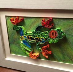 """Tree Frog Quilling 2017. Hand quilled paper art size 4""""x 6"""", white frame size 6.5"""" x 8.5 """" (Matted to 5""""x7"""" if you want to change frames.) The leaf background is hand sketched in color pencil and all the art is sprayed in UV and moisture resistant clear coat for protection. Elizabeth Shea Design on Facebook"""