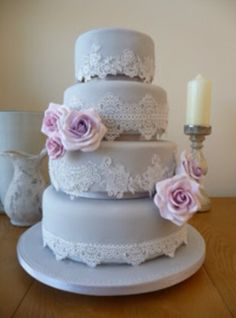 Grey wedding cake with lace icing and flowers