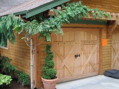 Adding a trellis over the garage doors adds interest and additional design detail to the facade of a home.  This picture shows a wisteria vine, but any large vine could be utilized.