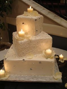 A three-tier wedding cake decorated with silver beads, handcrafted petals made from fondant and glasses with candles to show romance is in the air.
