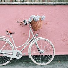 all white bicycle (umm, yes?!) with flowers in front of a pink wall | good vibrations for spring