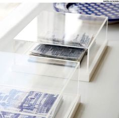 Colocados em caixas de acrílico, cadernos de anotações, diários de viagens e agendas antigas podem se tornar objetos de decoração. Projeto de Mariana Tassinari, Bruna Albuquerque e Lívia Ribas.