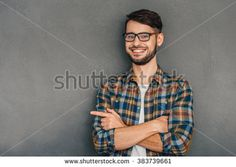 This is my choice! Cheerful young man in glasses pointing at copy space and looking at camera with smile while standing against grey background - stock photo