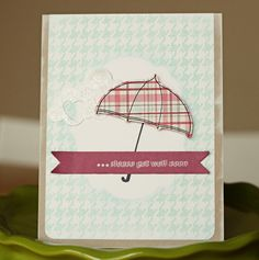 """I created a mask in the middle of my white mat, stamped a houndstooth pattern, and used an ink blending tool to smudge more ink around the mask.  I wanted to make sure that when I removed the masking paper, the outline of the label shape would be prominent.      The umbrella, from PTI's """"scattered showers,"""" is so cute in plaid!  I adhered it over some glittery clouds :)"""