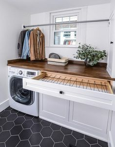 Topped with a stained wood countertop, white shaker cabinets accented with oil rubbed bronze hardware are fitted with a pull out drying rack. Modern Laundry Rooms, Laundry Room Layouts, Mudroom Laundry Room, Laundry Room Remodel, Laundry Room Organization, Laundry In Bathroom, Laundry Room Drying Rack, Laundry Room Floors, Vintage Laundry Rooms